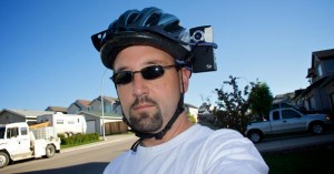 Man with camera attached to cycle helmet